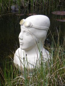 stone carving of the head of a swimmer emerging from the water